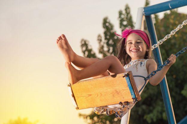 Little Girl Swinging At Sun Set