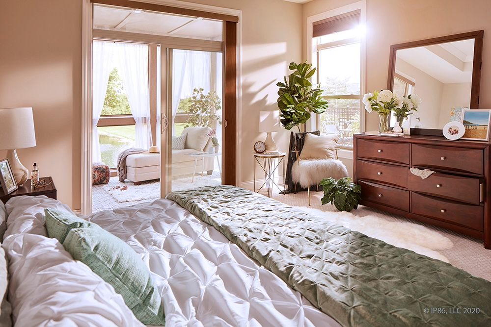 Epcon_Interior_Verona_Muirfield_Bedroom:Verona bonus model showing the view from the owner's suite to the screened-in porch and the courtyard.