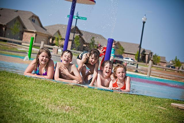 Children playing in a pool around our new homes in Moore OK from Ideal Homes