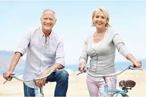 older couple with bikes on the beach