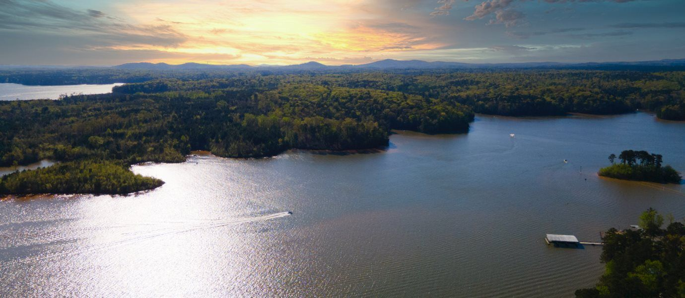 A wideshot of Allatoona Lake at sunset, surrounded by trees