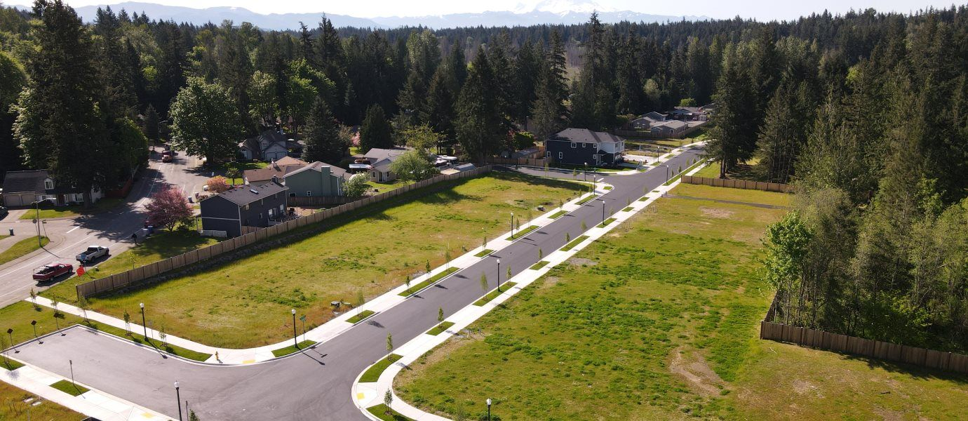 An aerial view of a t-shaped street surrounded by grass and homes