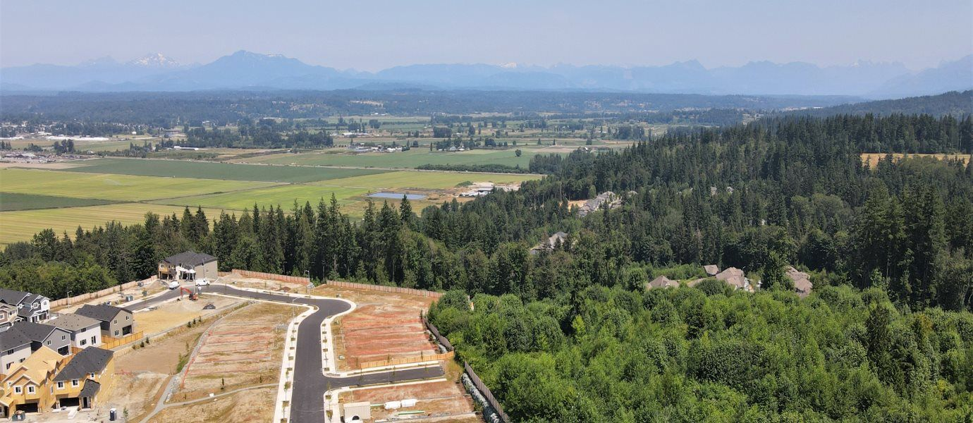 An aerial view of the community, which is surrounded by pine trees and features a mountainscape in t