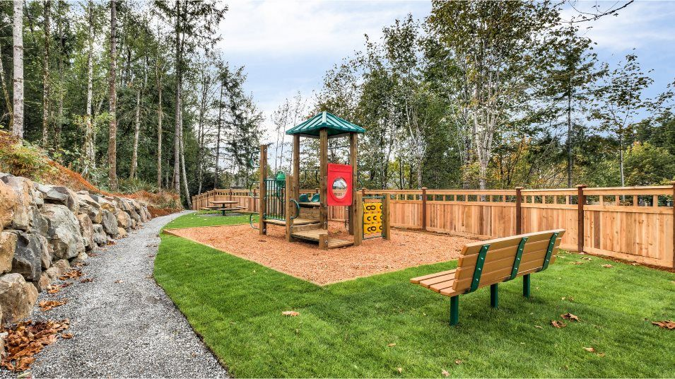 A park with a patch of grass, a playset and a bench