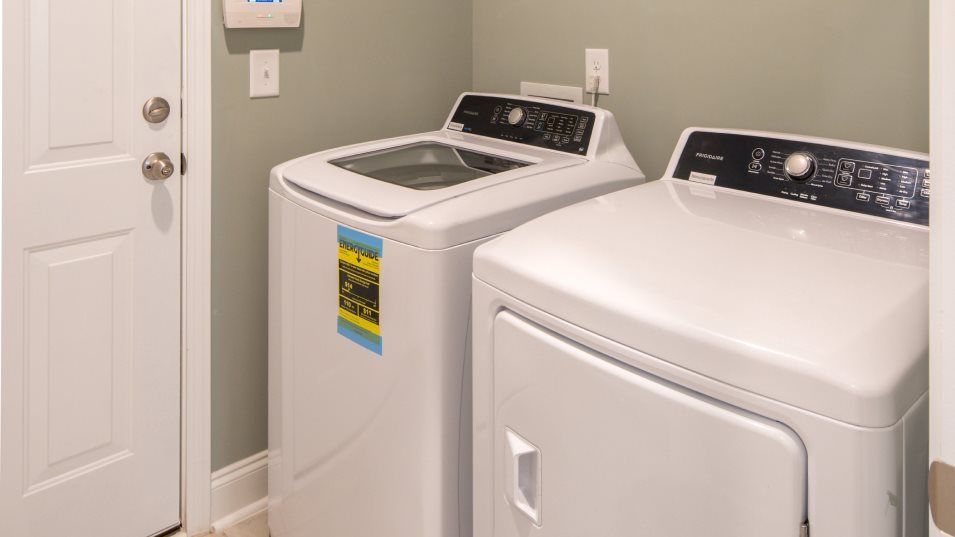Brunswick Plantation MUIRWOOD Laundry:A convenient laundry room comes with ceramic tile flooring, shelving and hookups for a washer and dr