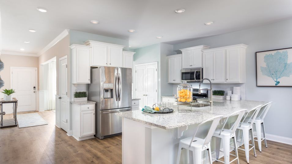 Brunswick Plantation KENSINGTON Kitchen:This modern kitchen features a center island with a double sink, designer-selected cabinetry and a p