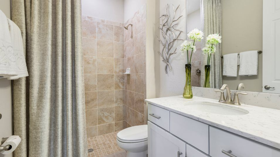 Heritage-Landing Executive Homes Victoria Bathroom:The shared bathroom includes a stylish, tile-covered walk-in shower, plenty of cabinet space and a g