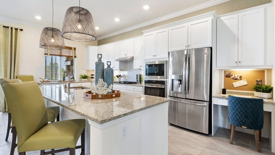 Vista-WildBlue Executive Homes Angelina Kitchen:Abundant natural light and counter space join an oversized granite-topped island to create a kitchen
