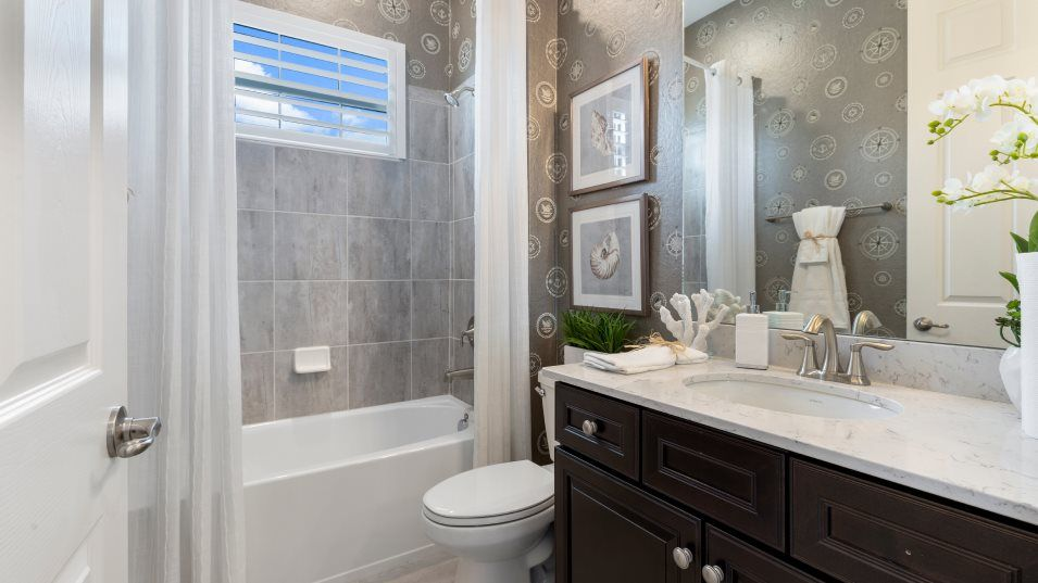 Heritage Landing Manor Homes The Princeton Bathroo:A charming, shared bathroom, this space features a shower-tub combination and a granite vanity topw