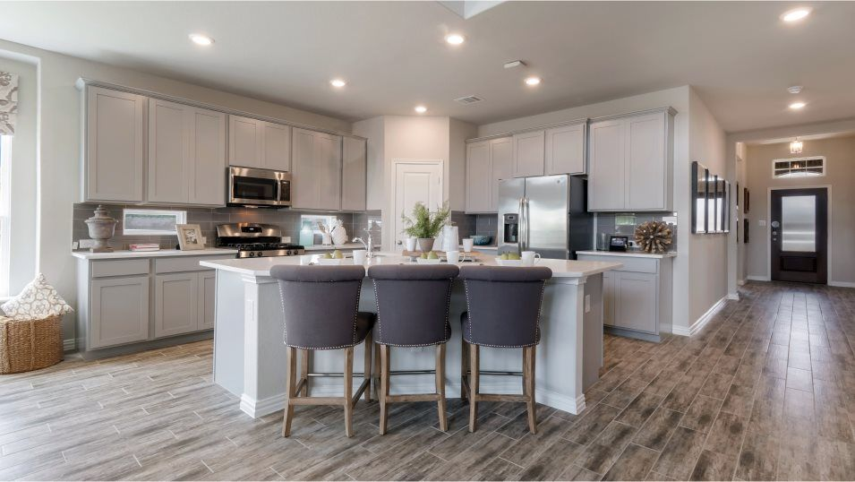 Built-in appliances include an over-the-stove micr:The modern kitchen has an open layout and a granite-topped island that overlooks the dining room and