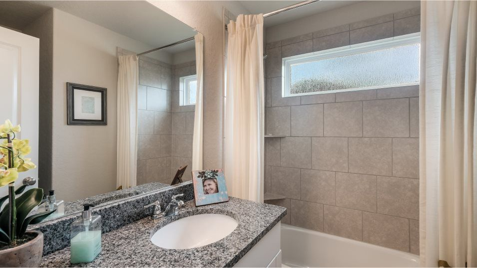 Waterwheel Barrington & Watermill Collection Thaye:The secondary bedrooms share a full bathroom with chrome faucets and a tub with tile surround