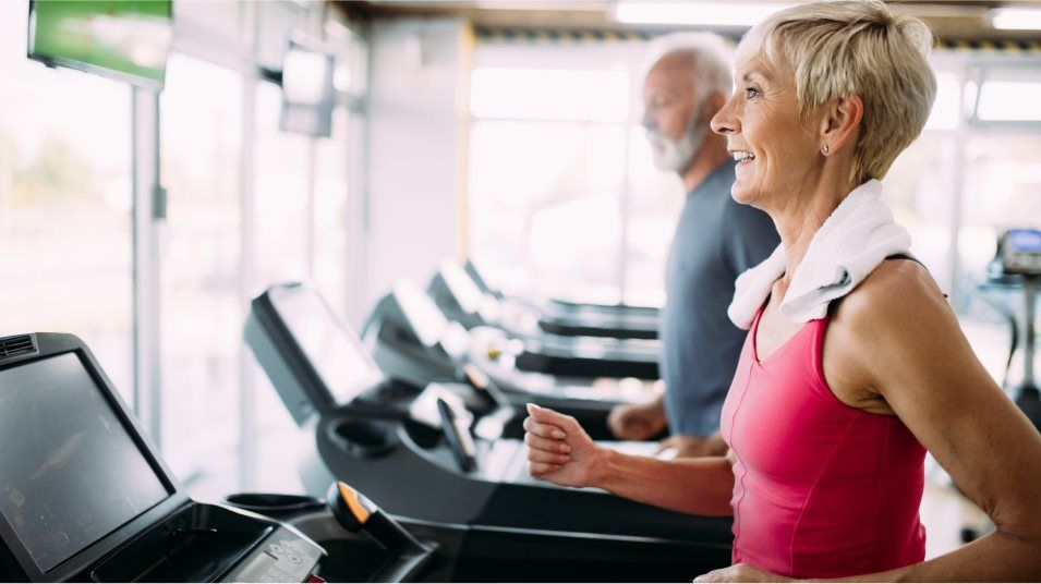 Two people using a treadmill