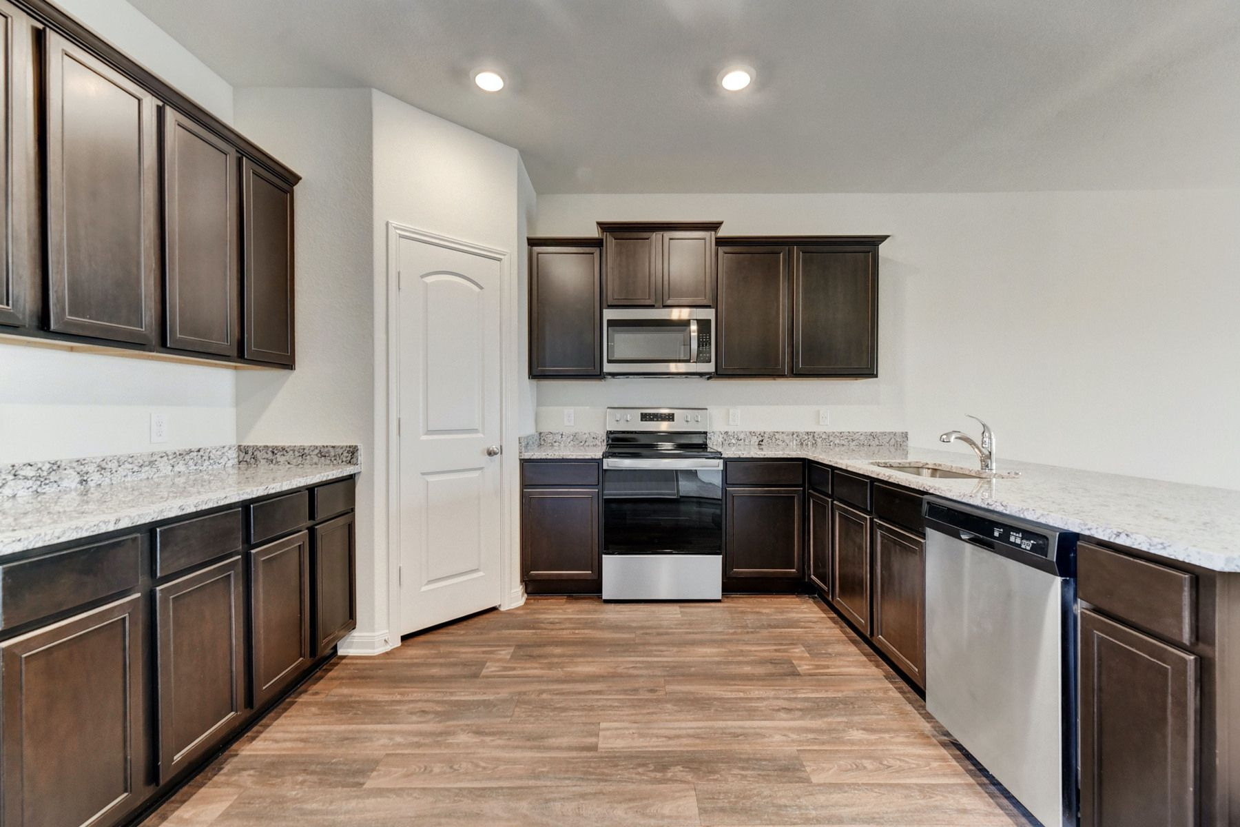The Travis by LGI Homes:Enjoy stunning granite countertops and designer wood cabinetry in this kitchen.