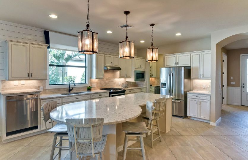 Martin Ray:Kitchen with rounded island and stainless steel appliances