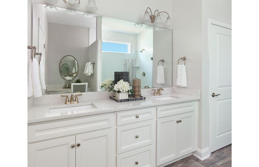 Summerwood:Owner's bath appointed with white cabinets, double sink and quartz countertops along with a frameles