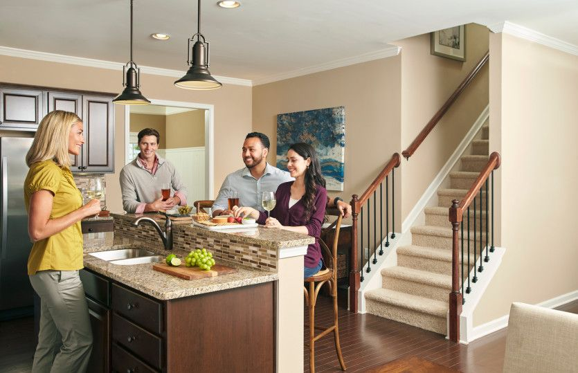 Exterior:Friends gather together around the newly built kitchen island in the Sandhill