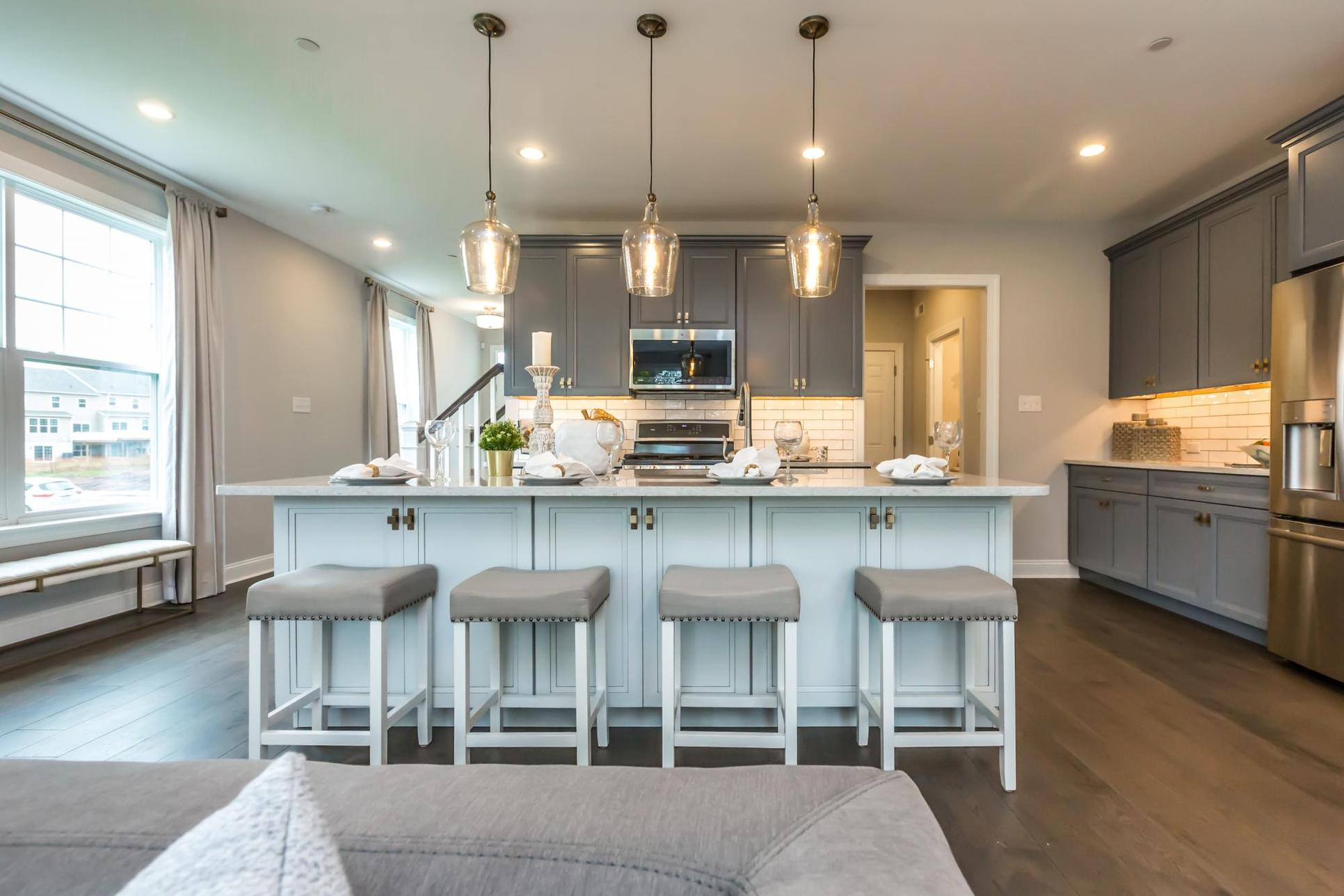 Brightly lit Kitchen with extended kitchen island with décor, a microwave and gray upper cabinets:Enclave at Ridgewood, Sutton Grand, Townhomes, Kitchen