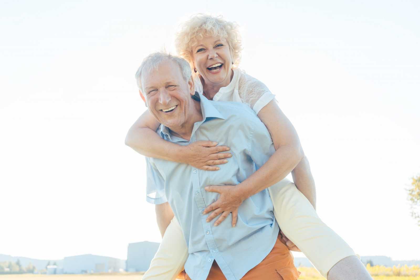 Happy senior man laughing while carrying his partner on his back:Low-angle view portrait of a happy senior man laughing, while carrying his partner on his back in a sunny day of summer in the countryside